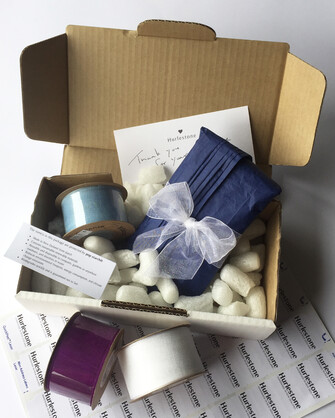 Postage box with ribbon, products and fill